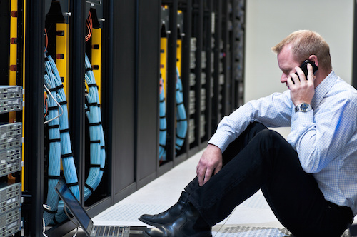 businessman with laptop and a smartphone in network server room